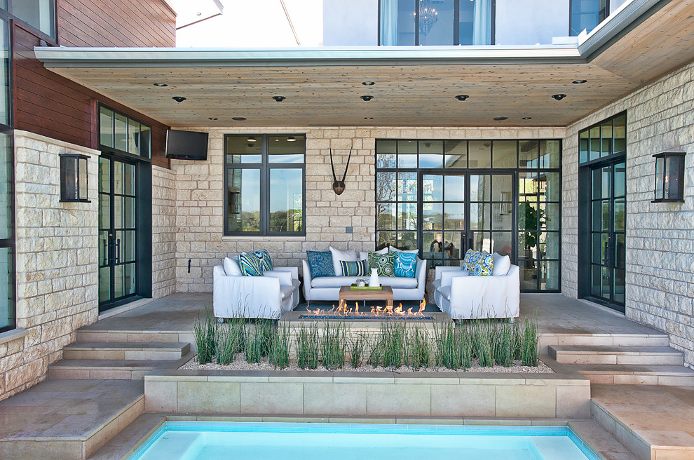 Inspiration for a contemporary patio remodel in Austin with a fire pit and a roof extension