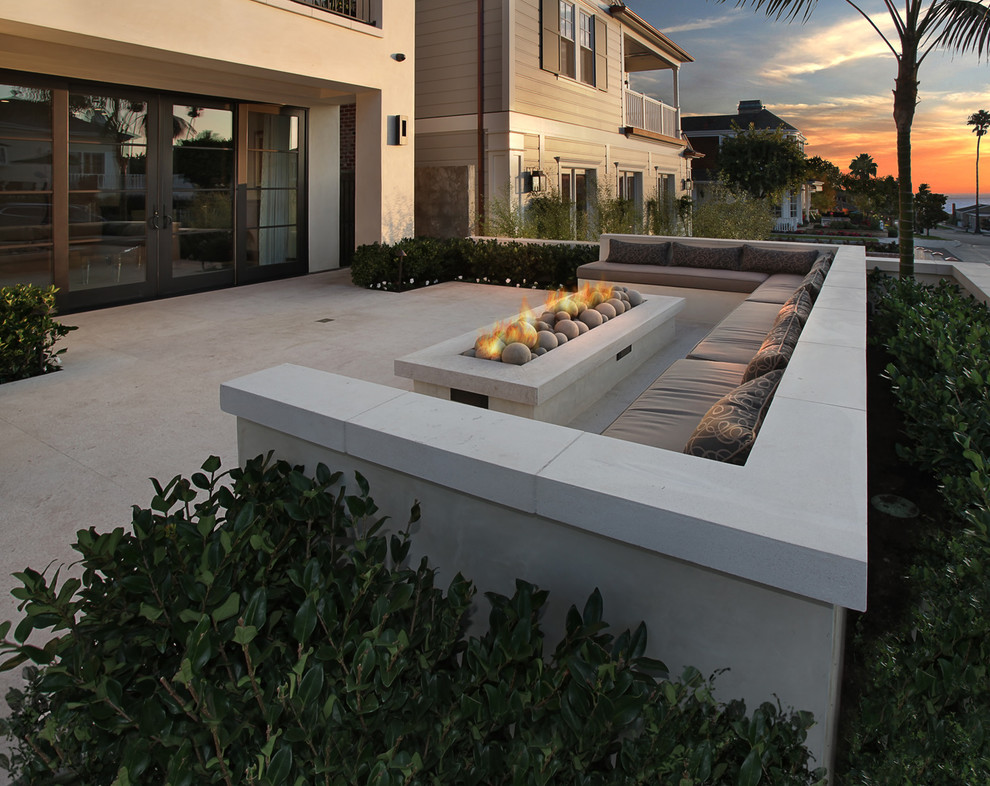 Example of a large trendy courtyard concrete patio design in Orange County with a fire pit and no cover