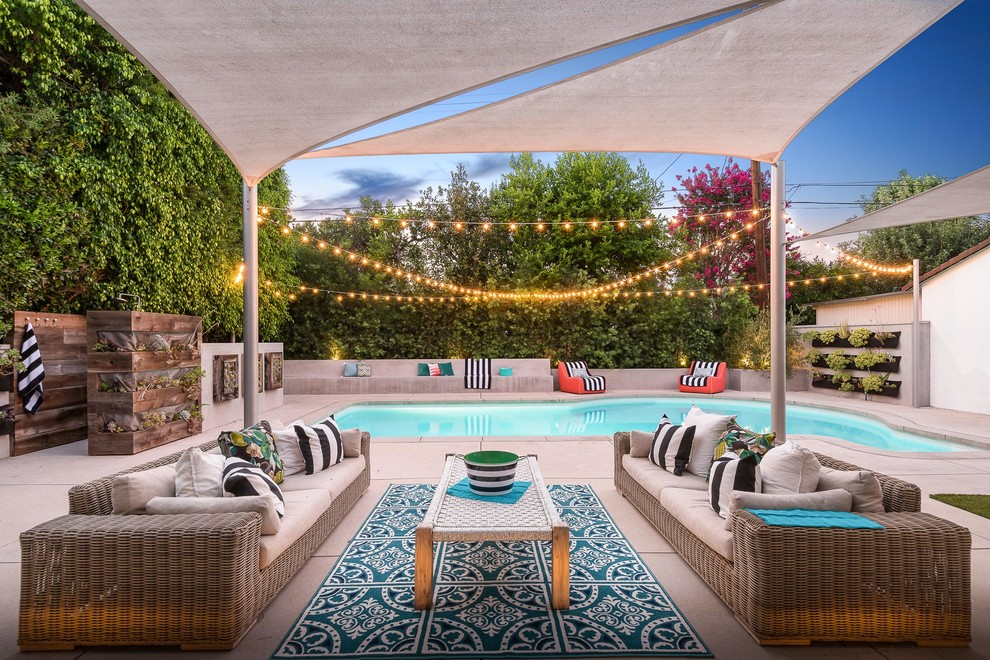 Inspiration for a contemporary backyard concrete paver patio container garden remodel in Los Angeles with an awning