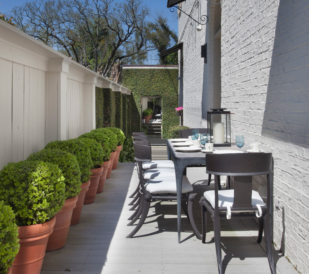 Elegant side yard patio container garden photo in New Orleans with decking and no cover