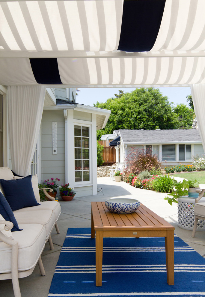 Patio - large coastal backyard stamped concrete patio idea in Los Angeles with a pergola
