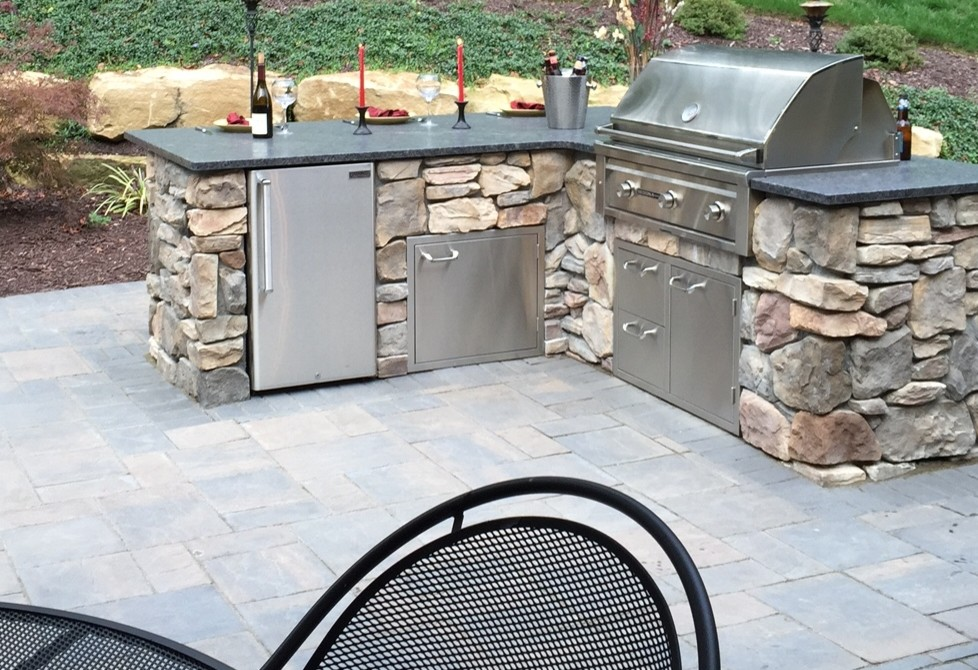 Example of a large classic backyard concrete paver patio design in Other with no cover and a fire pit