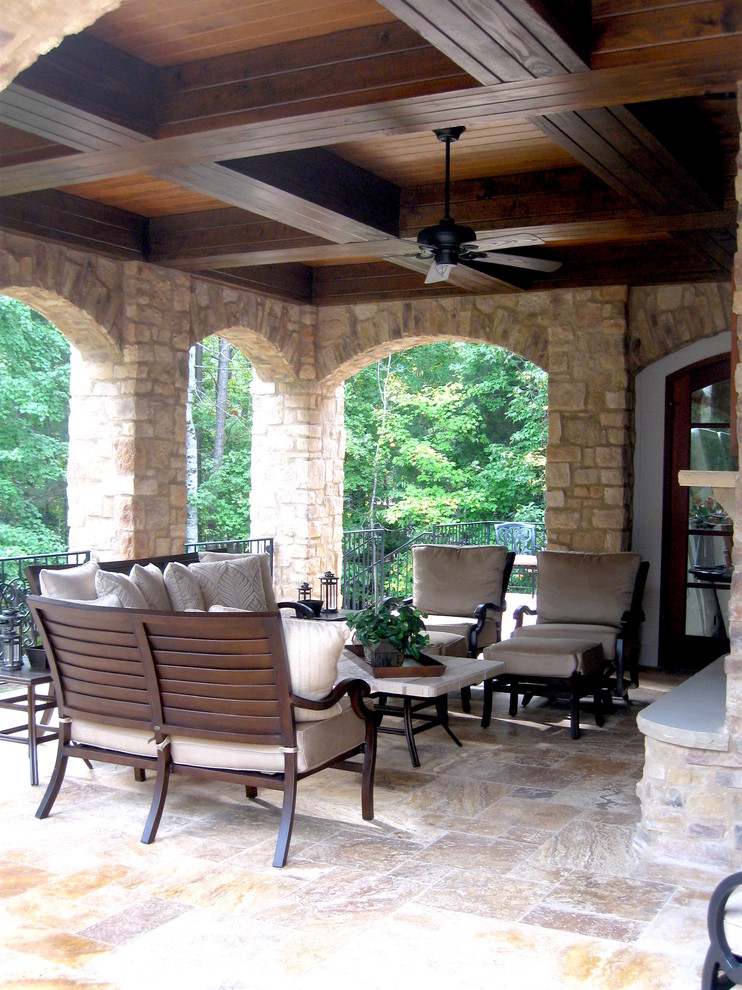 Example of a large classic backyard stone patio design in Raleigh with a roof extension