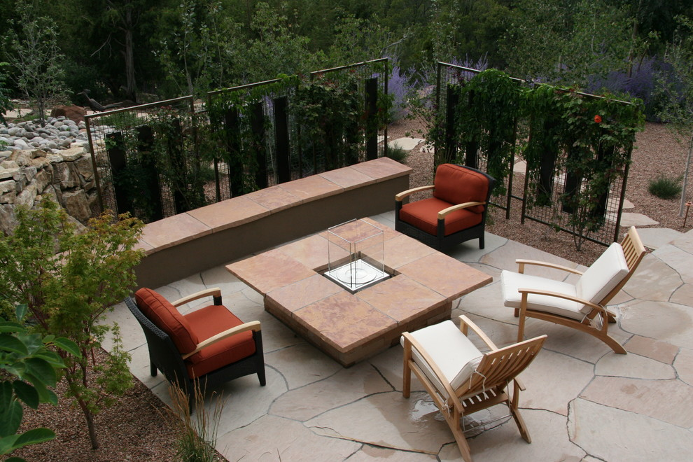 Inspiration for a contemporary backyard stone patio remodel in Albuquerque with a fire pit