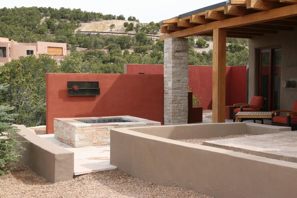 Example of a trendy backyard stone patio fountain design in Albuquerque