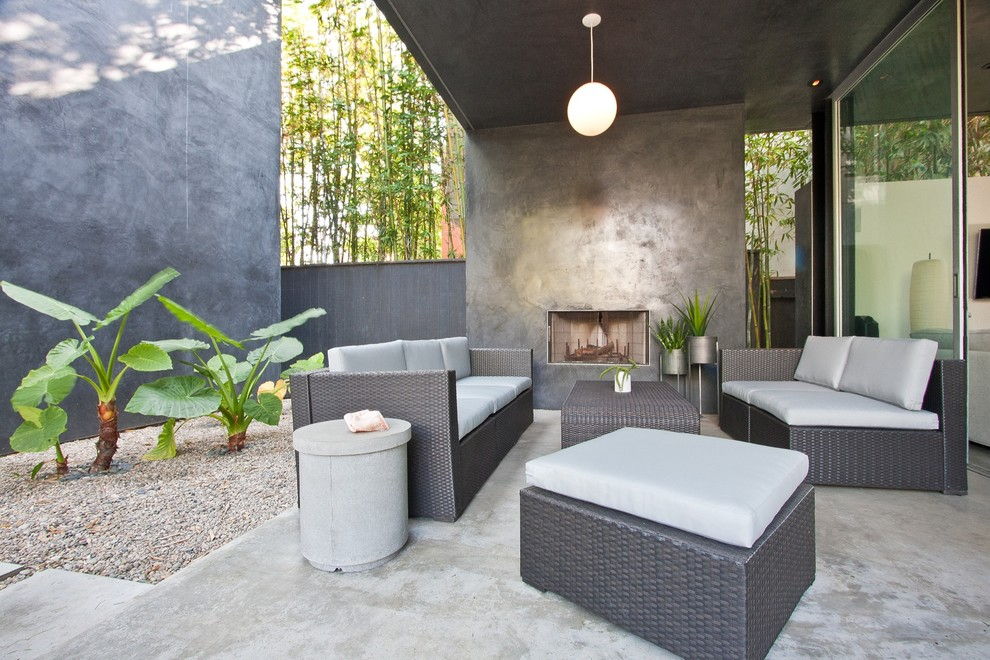 Inspiration for a mid-sized contemporary courtyard concrete patio remodel in Los Angeles with a fire pit and a roof extension