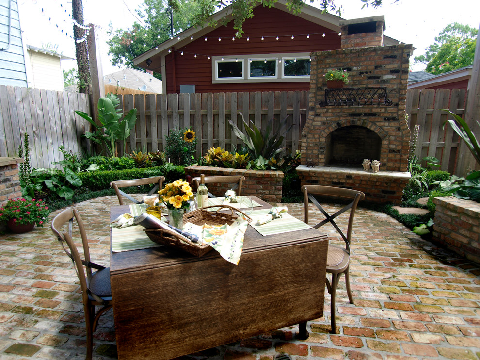 Large elegant backyard brick patio photo in Houston with a fire pit and no cover