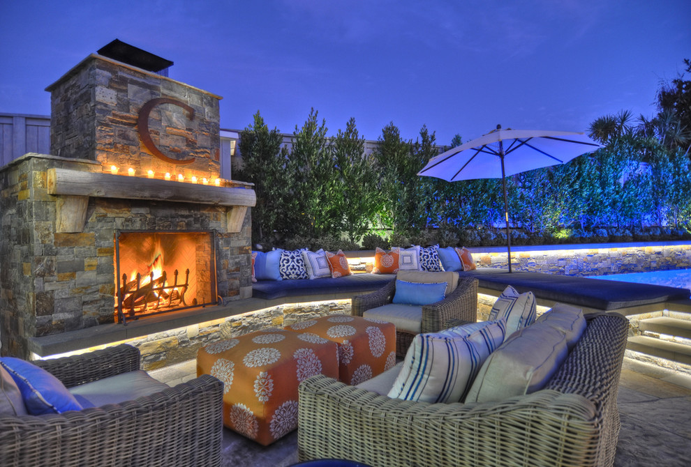 Example of a classic patio design in Orange County with a fire pit and no cover