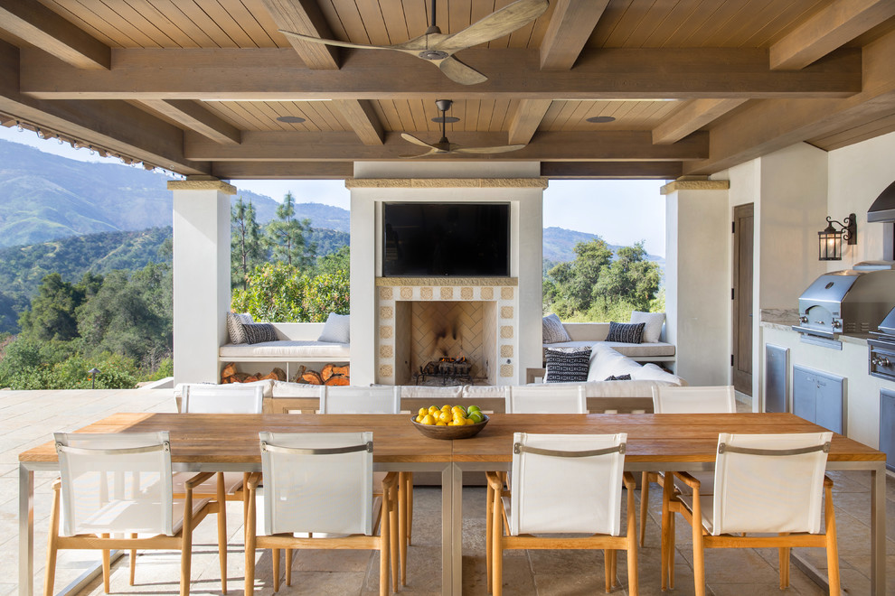 Inspiration for a large mediterranean backyard tile patio kitchen remodel in Santa Barbara with a roof extension