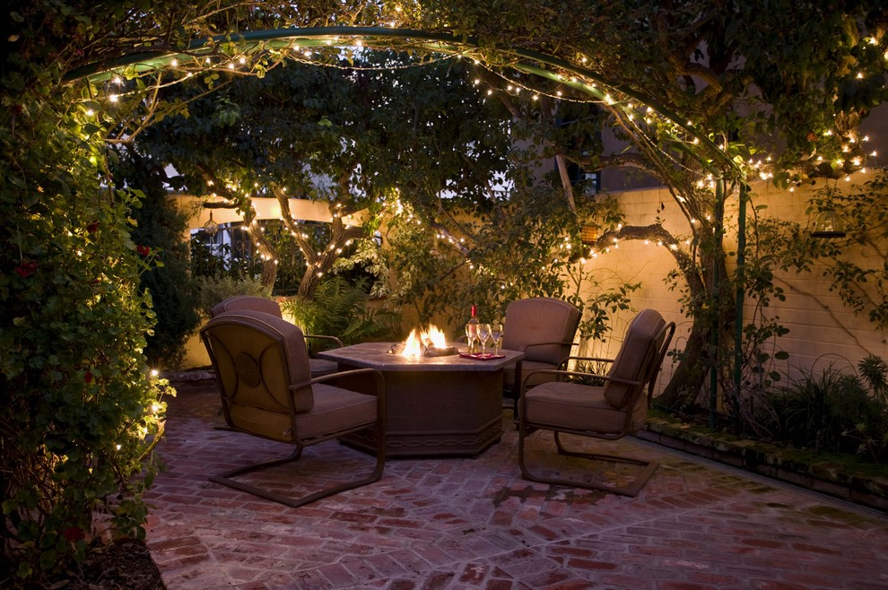 Example of a mid-sized classic courtyard brick patio design in Orange County with a fire pit and no cover