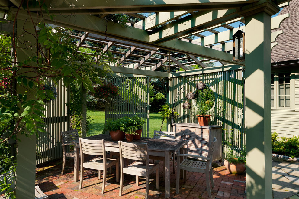 Example of a farmhouse courtyard patio design in New York with a pergola