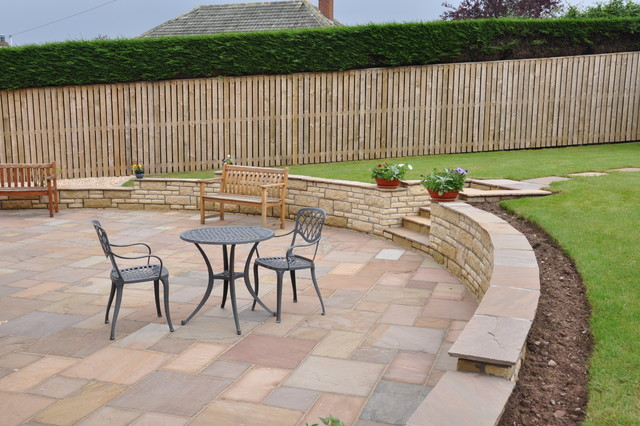Beautiful Curved Sandstone Patio With Steps Leading To Lawn Area Traditional Patio