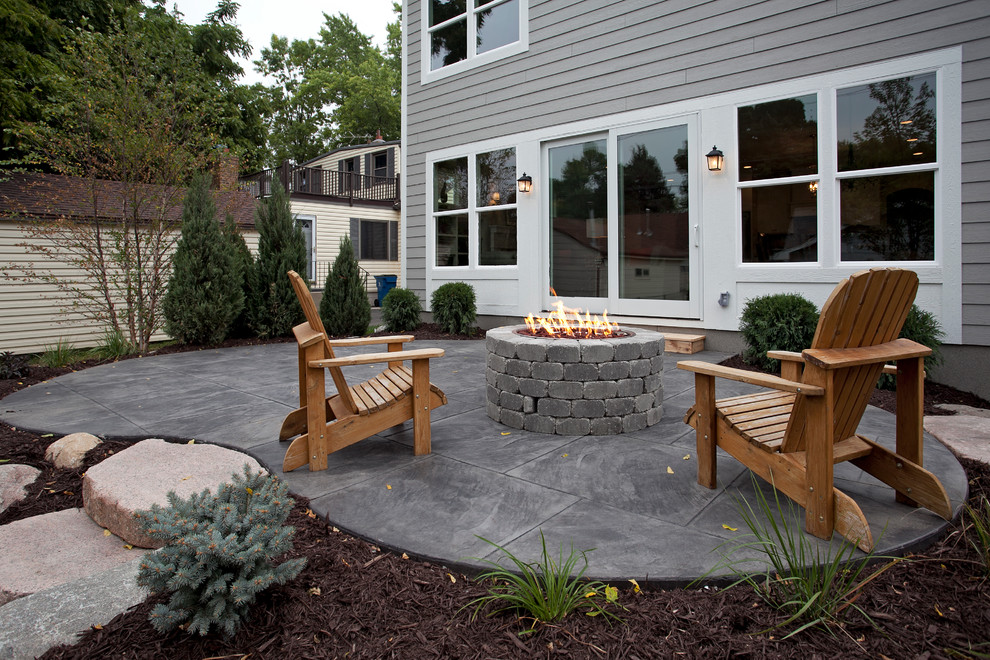 Inspiration for a large timeless stamped concrete patio remodel in Minneapolis with a fire pit and no cover