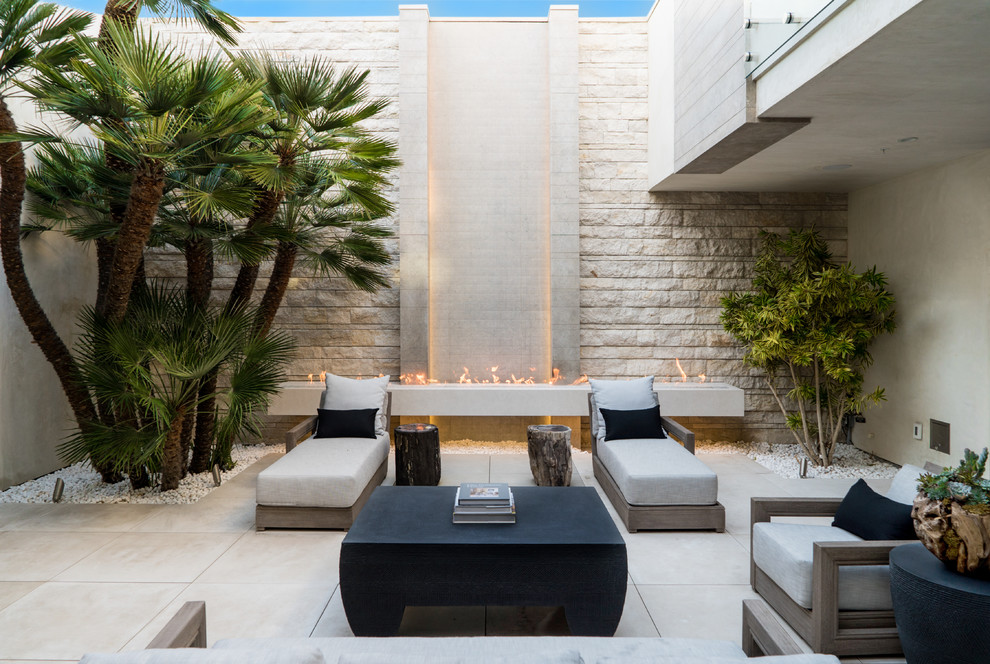Example of a large trendy courtyard tile patio design in Phoenix with a fireplace