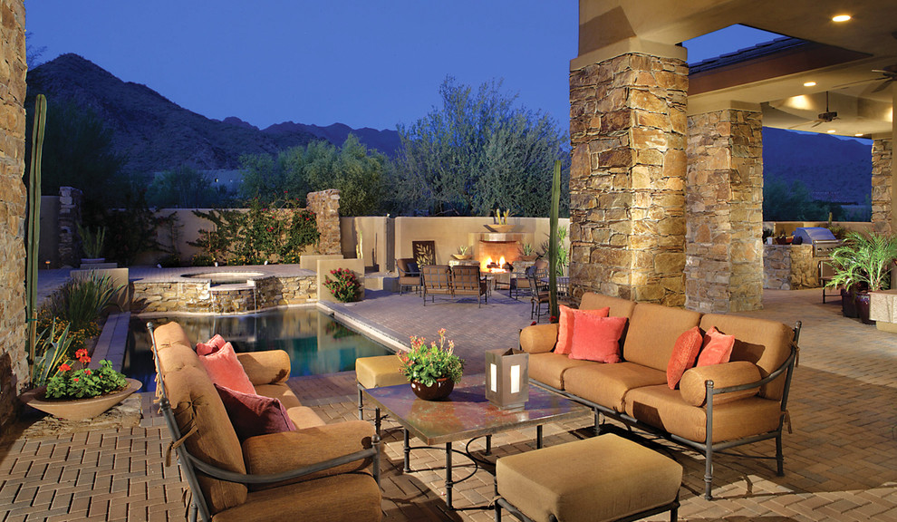 Inspiration for a mid-sized southwestern backyard brick patio remodel in Phoenix with a fire pit and no cover