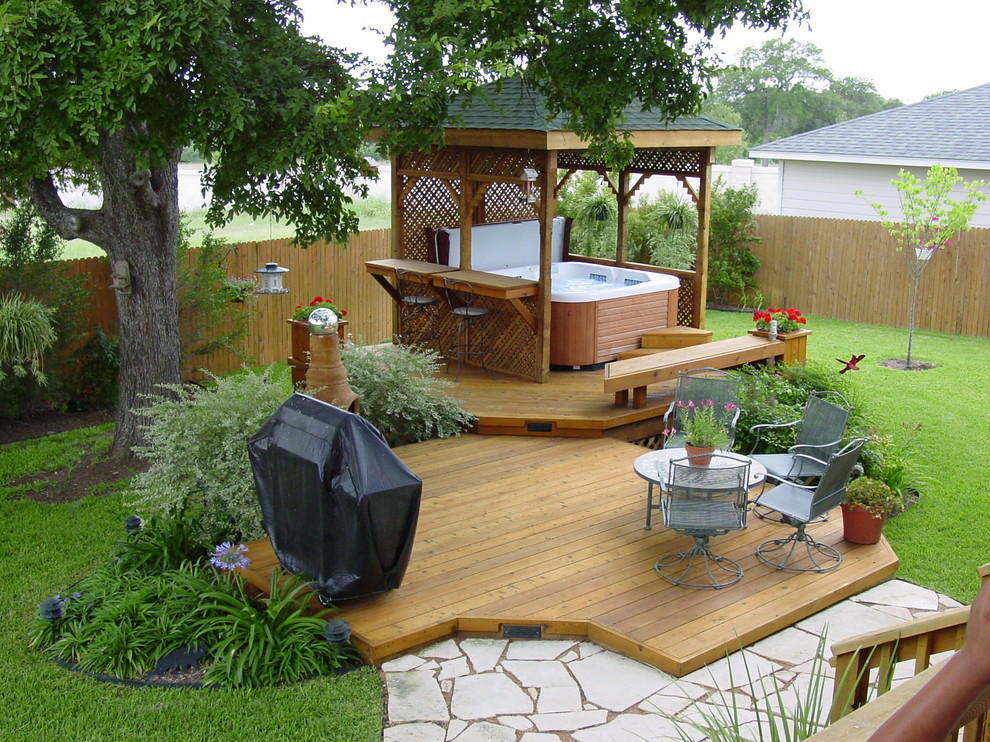 Large trendy backyard patio fountain photo in Austin with decking and a pergola