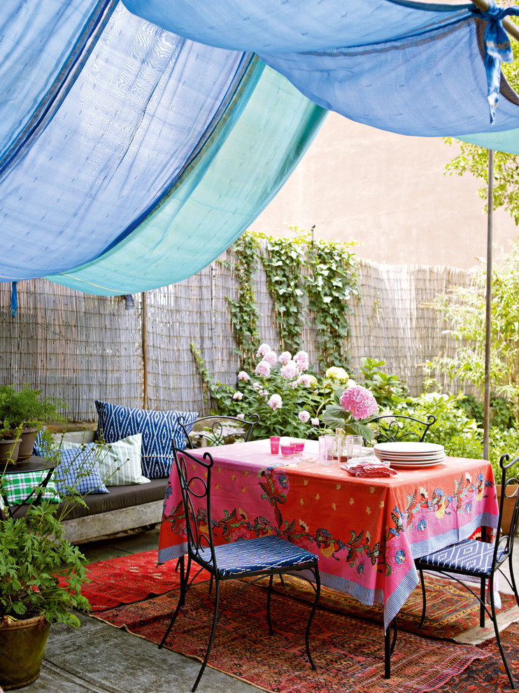 Inspiration for an eclectic patio remodel in Other with an awning