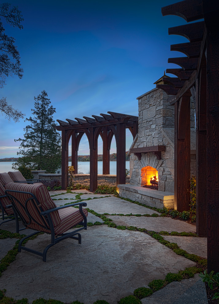 Inspiration for a mediterranean patio in Detroit with natural stone paving and a fire feature.