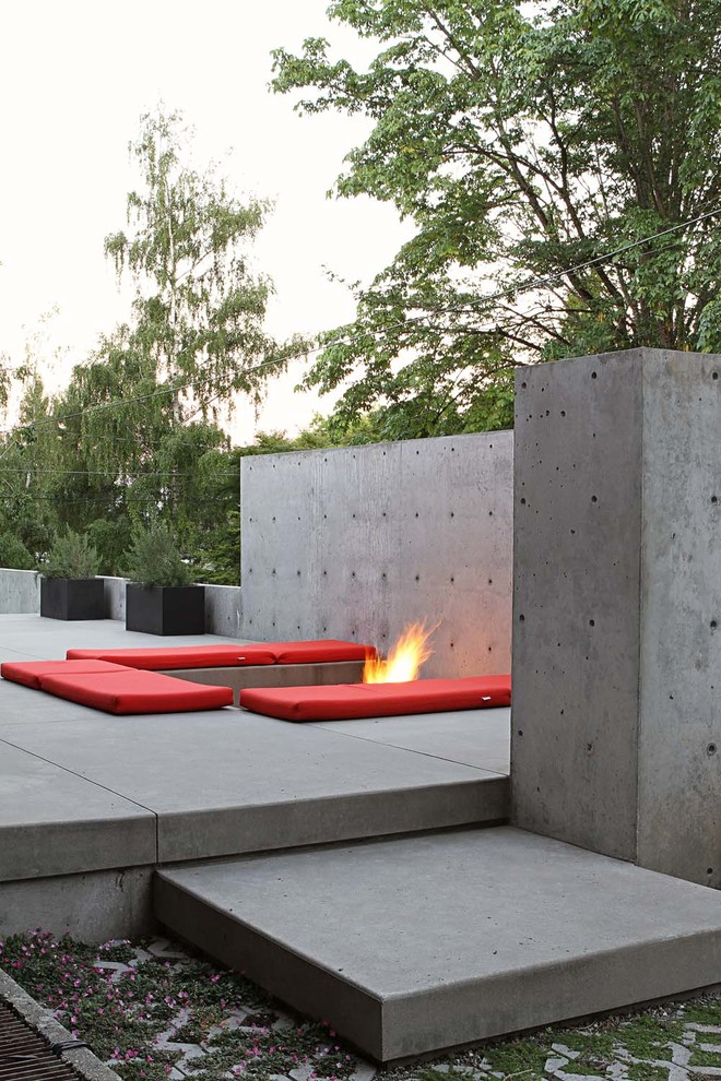 Example of a large trendy backyard concrete patio design in Seattle with a fire pit and no cover