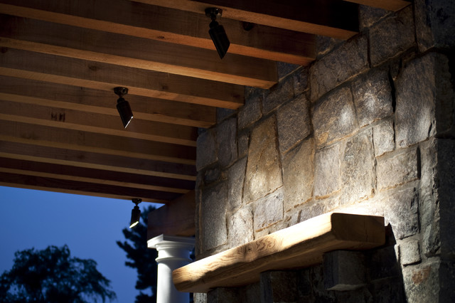 Directional outdoor lighting on stone fireplace - traditional
