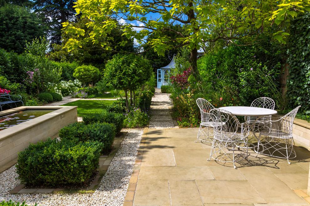 Patio - mid-sized traditional backyard stone patio idea in London