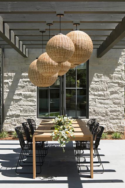 Example of a coastal backyard tile patio design in Orange County with a pergola