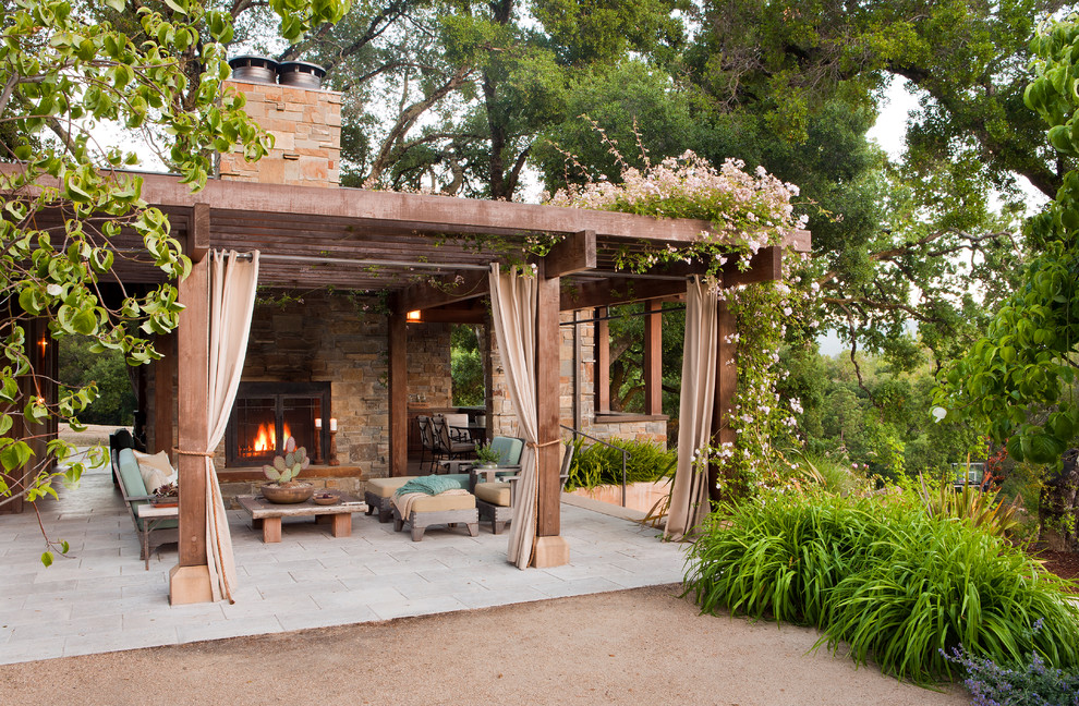 Example of a mid-sized tuscan backyard stone patio design in San Francisco with a pergola and a fireplace