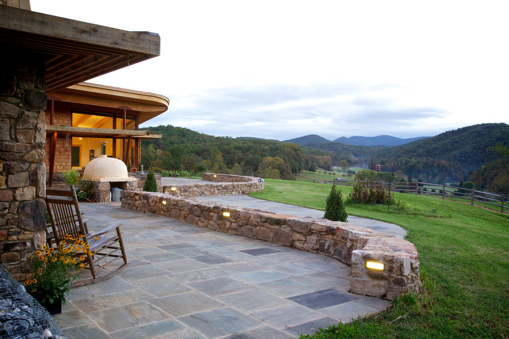 Example of a mountain style backyard stone patio design in Portland Maine with no cover and a fire pit