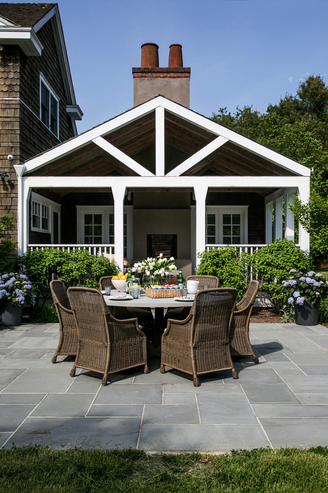 Huge beach style backyard stone patio container garden photo in New York with a roof extension