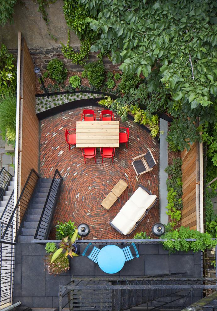 Small eclectic backyard brick patio photo in New York