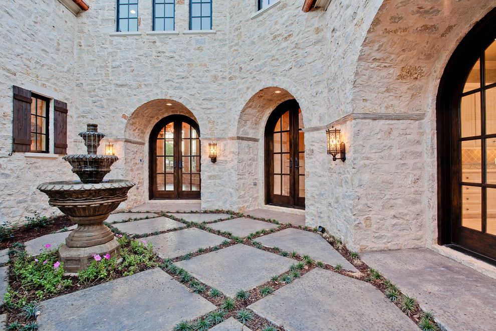 Example of a large tuscan courtyard concrete patio fountain design in Dallas with no cover