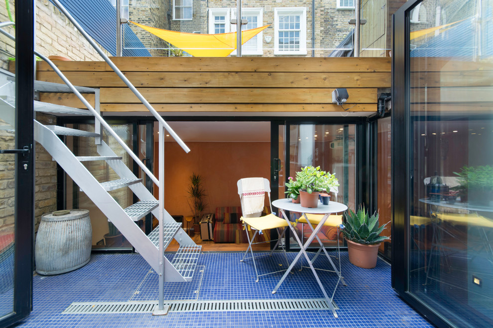 Foto di un patio o portico contemporaneo in cortile con un giardino in vaso, piastrelle e nessuna copertura
