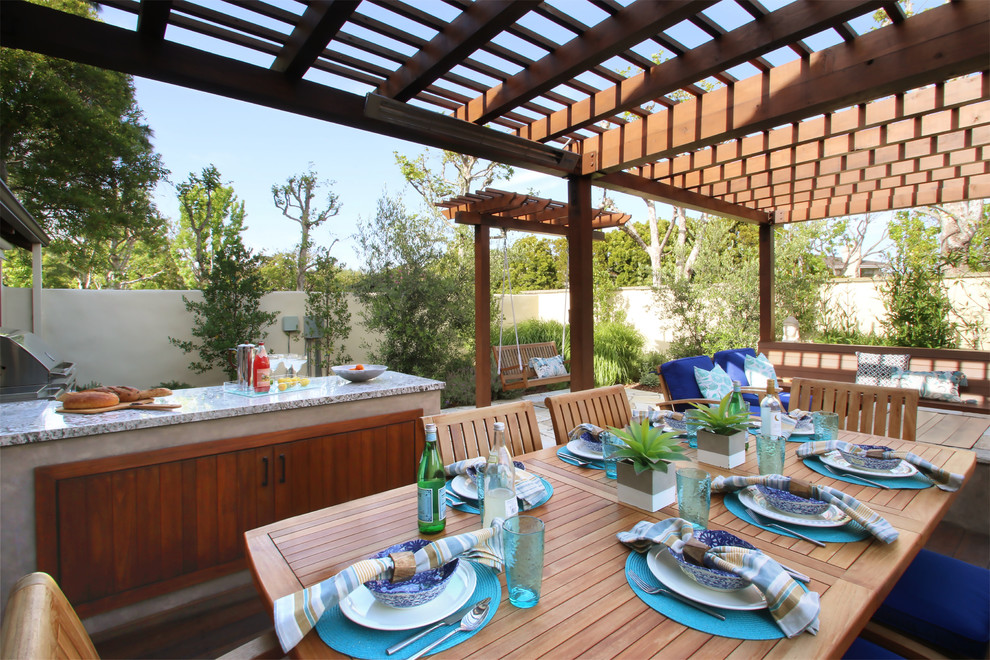 Patio kitchen - mid-sized transitional backyard stone patio kitchen idea in Los Angeles with a pergola