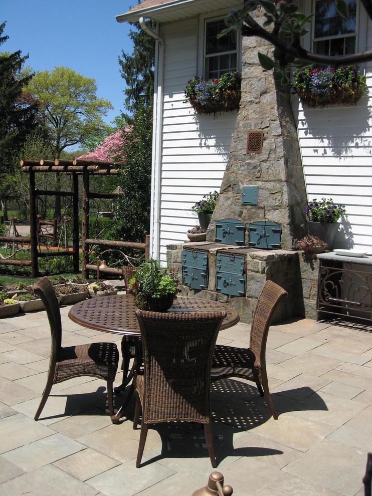 Patio - small traditional backyard stone patio idea in Newark