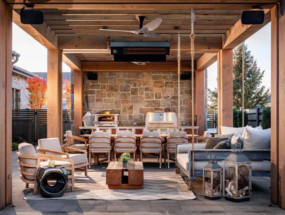 Modelo de patio campestre, extra grande, en patio trasero, con cocina exterior, adoquines de hormigón y pérgola
