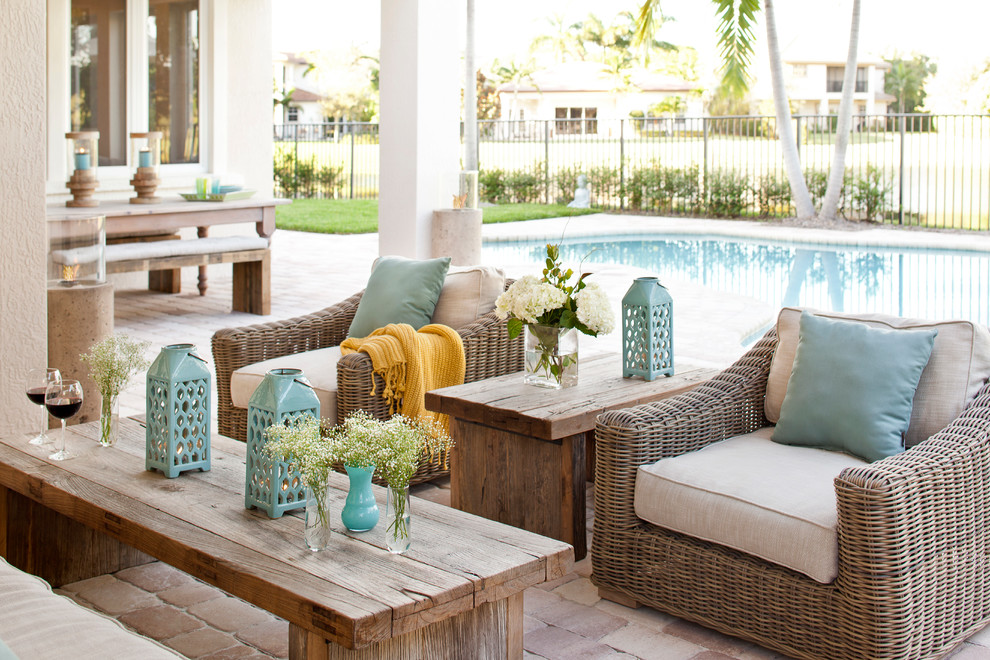 Patio - large transitional backyard brick patio idea in Miami with a roof extension