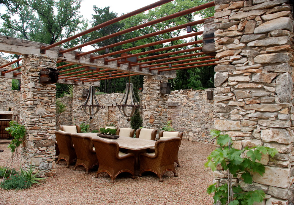 Example of a tuscan gravel patio design in Austin with a pergola