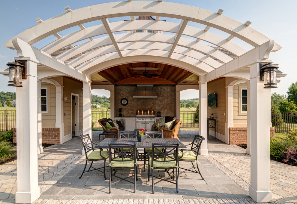 Elegant patio kitchen photo in Other with a pergola