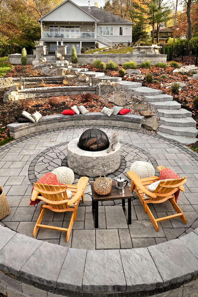 Patio - large traditional backyard stone patio idea in Boston with a fire pit and no cover