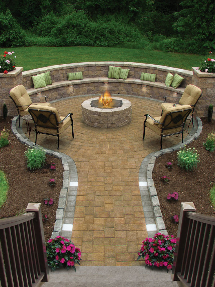 Example of a mid-sized classic backyard concrete paver patio design in Other with a fire pit and no cover