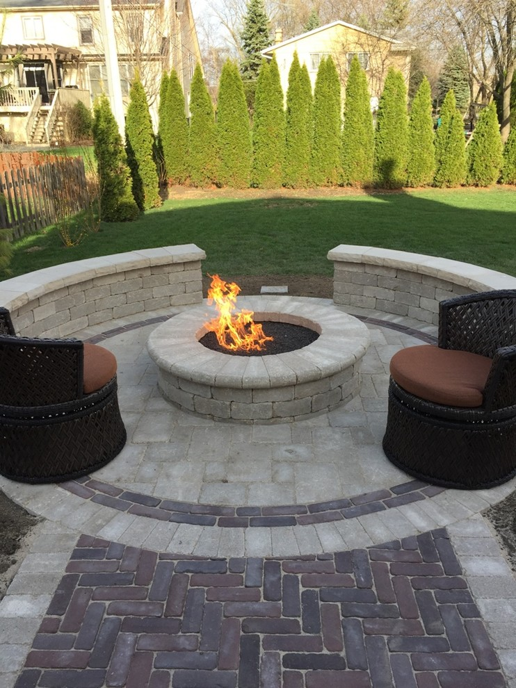 Patio - large traditional backyard stone patio idea in Chicago with a fire pit and no cover