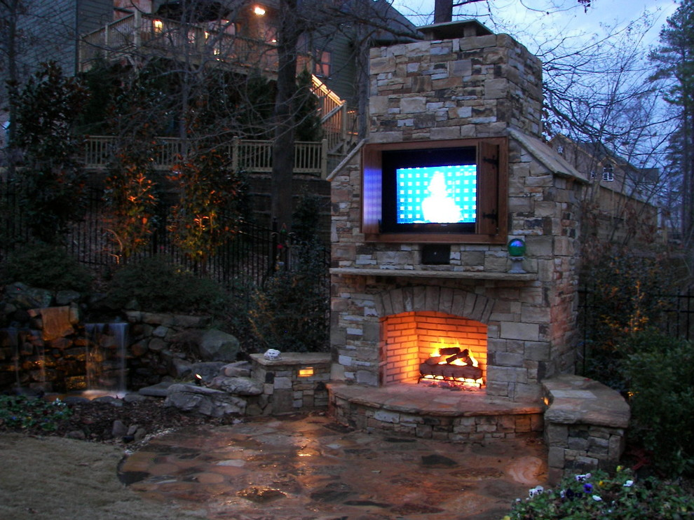 Fireplace with built in TV and water feature.  Landscape lighting