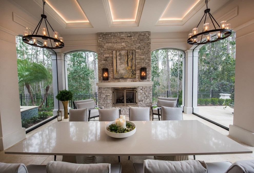 Patio - large transitional backyard patio idea in Orlando with a roof extension and a fireplace