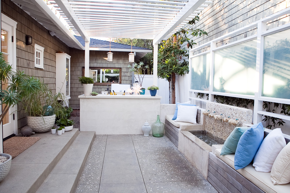Example of a classic patio fountain design in Los Angeles with a pergola
