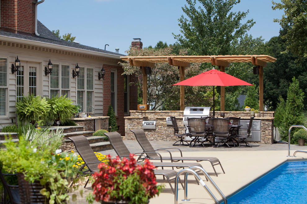 Inspiration for a mid-sized timeless backyard stone patio kitchen remodel in Charlotte with a pergola