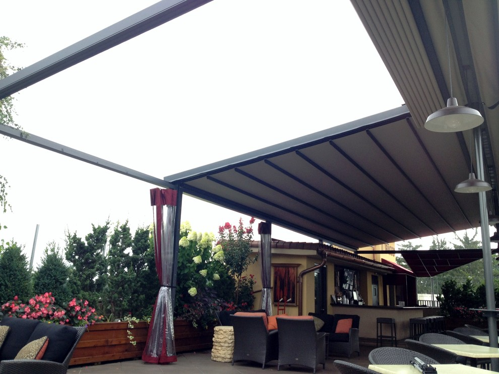 Example of a huge tuscan patio design in New York with a pergola