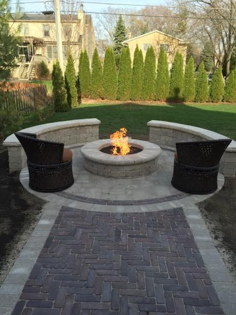 Mid-sized transitional backyard concrete paver patio photo in Chicago with a fire pit