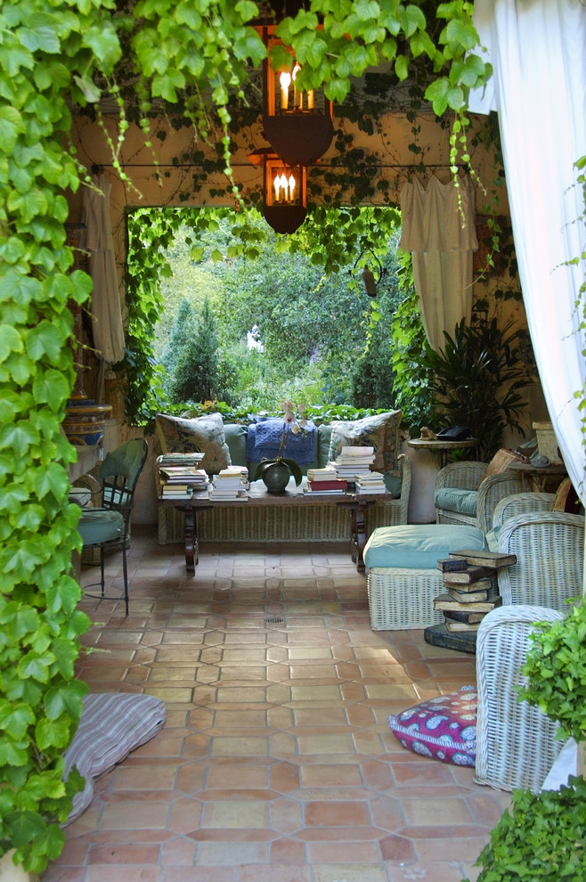 Patio - large french country backyard tile patio idea in Santa Barbara with a roof extension