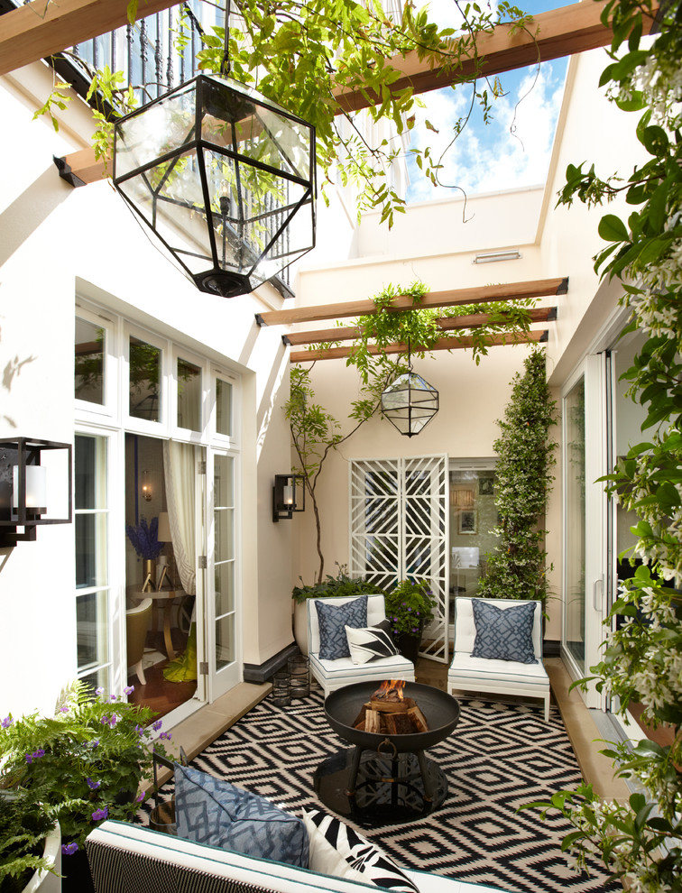 Tuscan courtyard patio photo in London with a fire pit and no cover