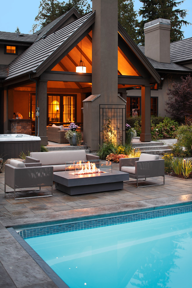Mid-sized trendy backyard concrete paver patio photo in Seattle with a fire pit and a roof extension